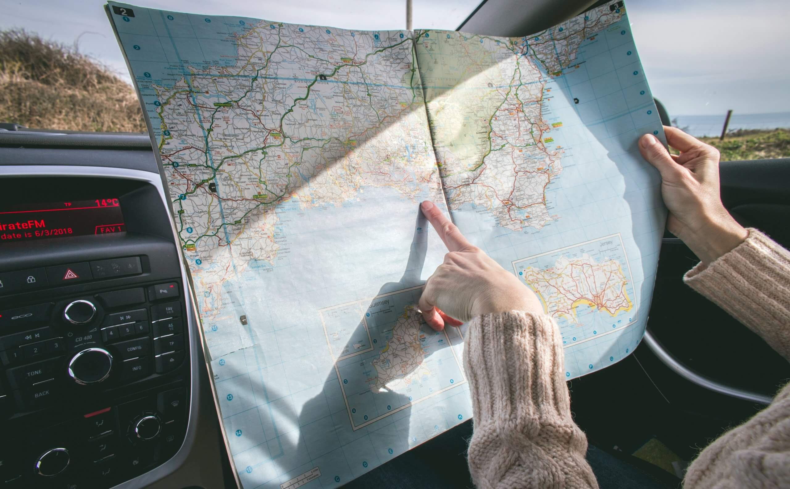 Person looking at map on road trip.